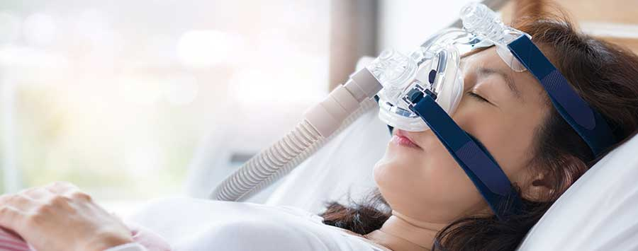 A woman sleeping with a CPAP machine on