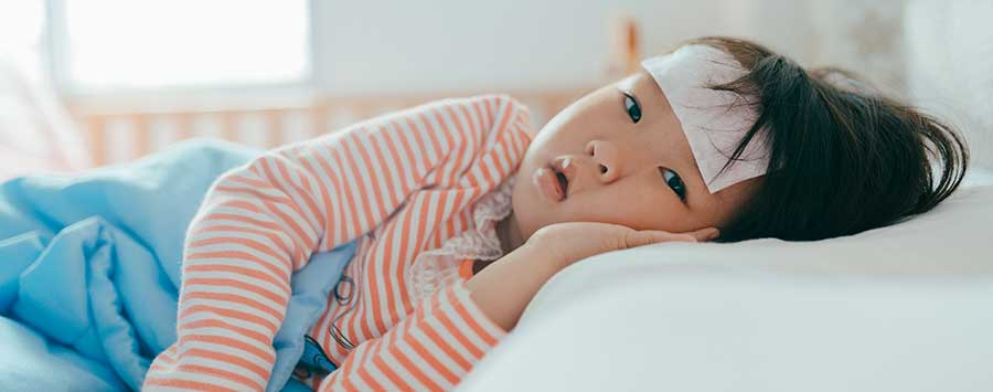 A child laying in bed with a cloth on their forehead.