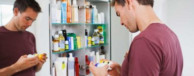 A man looking at pill bottles in a bathroom mirror