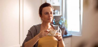 A person standing in a kitchen and sipping tea.