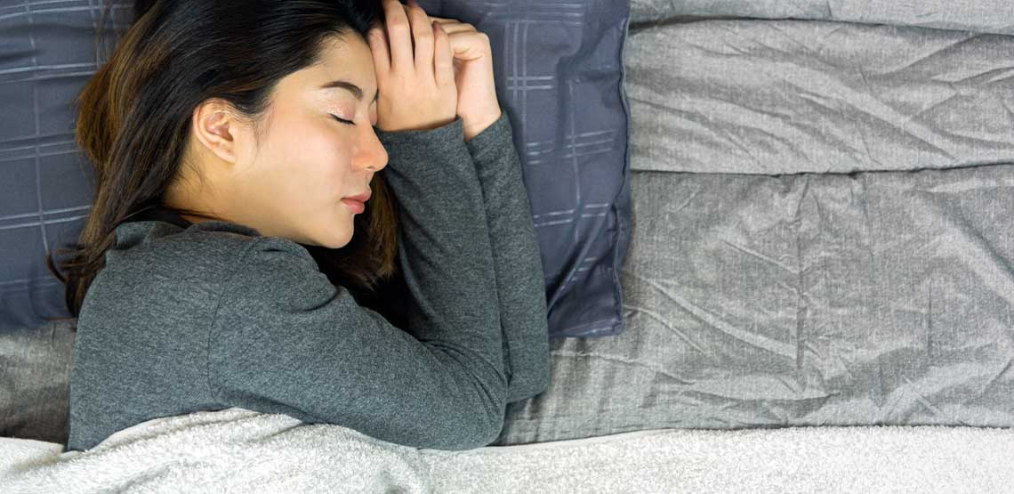 A person laying in bed with a grey quilt.