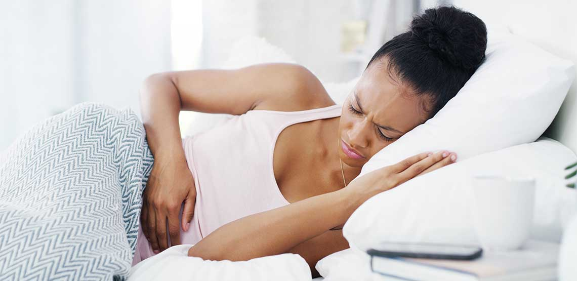 A woman laying in bed and clutching her stomach.