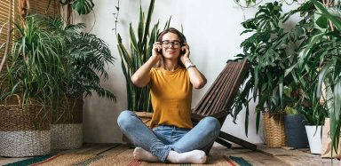 A woman sitting on the floor, surrounded by potted plants, listening to audio with headphones on.