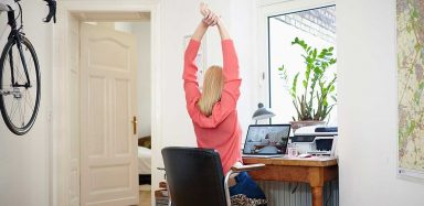 A woman sitting at her desk at home, raising her arms above her head to stretch.