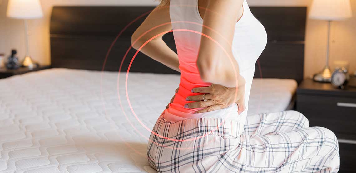 A woman sitting on a bed, holding her back, where red lines are showing pain points.