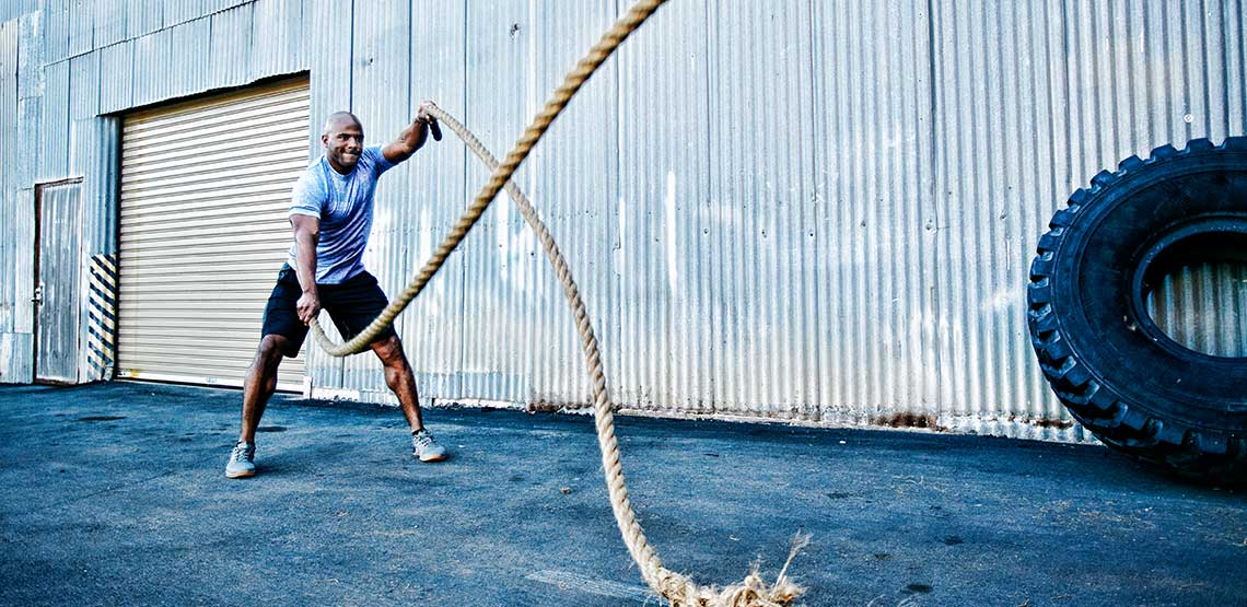 A man working out outside with heavy ropes.
