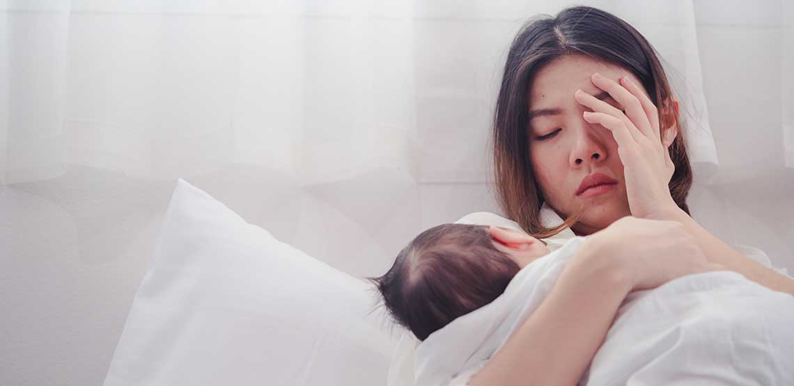 A young mother sitting bed holding her baby.
