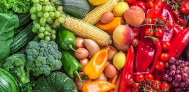Various fruits and vegetables arranged by colour from green to yellow, to red.